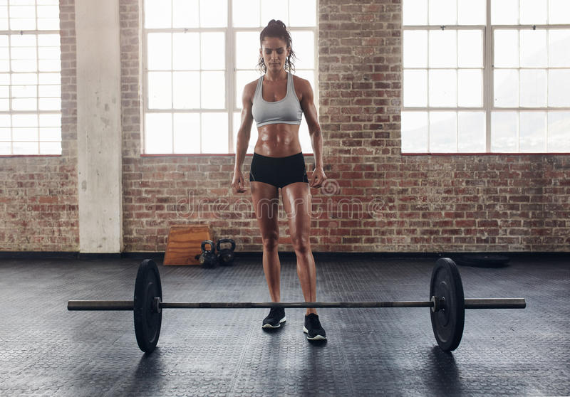 Fit young woman standing at gym with barbells on floor. Full length portrait of fit young woman standing at gym with barbells on floor. Tough crossfit female at royalty free stock images