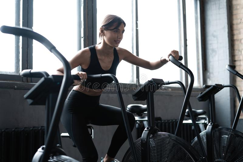 Fit young woman using exercise bike at the gym. Fitness female using air bike for cardio workout at gym stock photography
