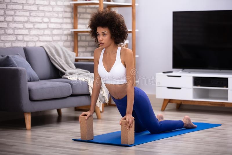 Woman Using Wooden Blocks While Doing Exercise stock photo