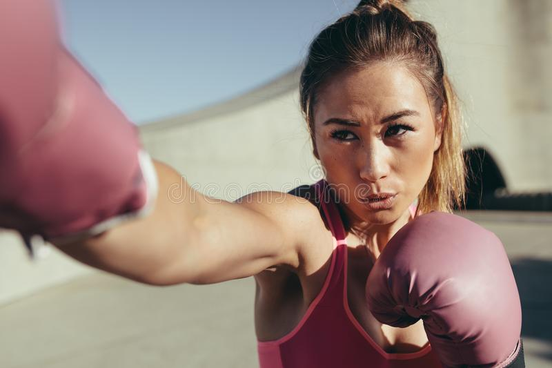 Female boxer practicing boxing outdoors royalty free stock photo