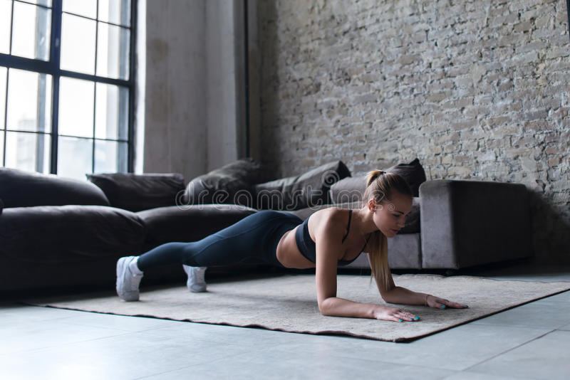 Fit young woman wearing sportswear working out at home doing planking exercise on carpet stock photo