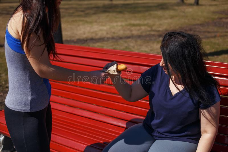 Fit young woman control her friend to stop eating junk food. Hea. Fit young women control her friend to stop eating junk food. Health care, weight loss, friendly royalty free stock images