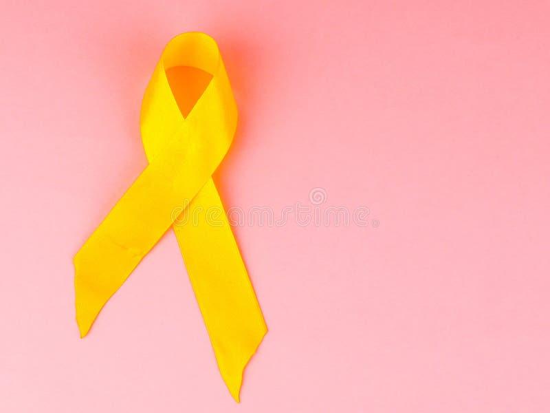 A fita amarela da conscientização do câncer como o símbolo da conscientização do câncer da infância, apoia a fita das tropas imagens de stock royalty free