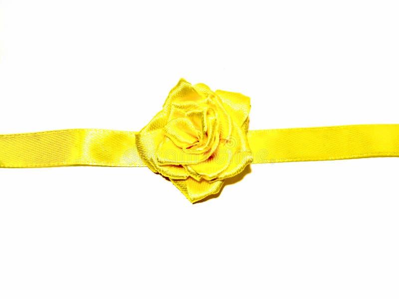 Fita amarela do cetim com a rosa no fundo branco imagem de stock