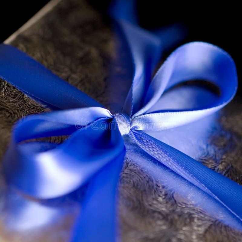 Fita azul amarrada em uma curva no presente de prata. fotografia de stock