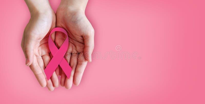 Fita cor-de-rosa nas mãos para a conscientização do câncer da mama fotografia de stock royalty free