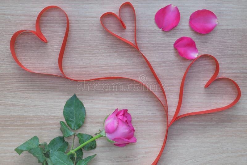 Fita da forma do coração de três vermelhos com as pétalas cor-de-rosa cor-de-rosa na superfície de madeira imagens de stock