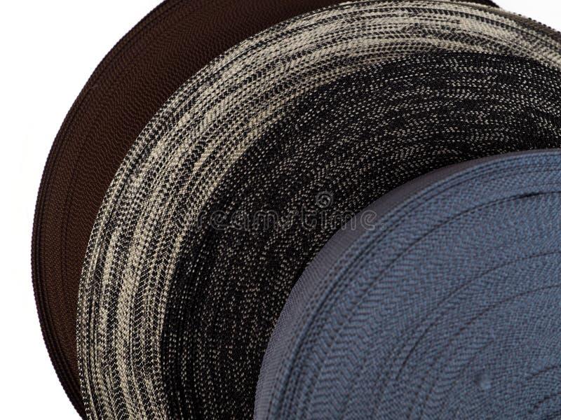 Fita de cores diferentes nas bobinas, muitas bobinas multi-coloridas para a indústria têxtil, fabricação da roupa foto de stock