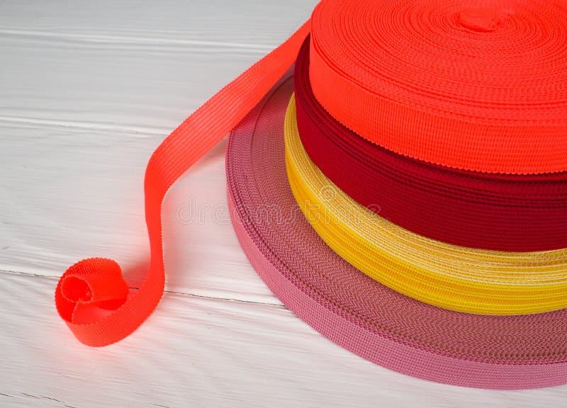 Fita de cores diferentes nas bobinas, muitas bobinas multi-coloridas para a indústria têxtil, fabricação da roupa imagem de stock