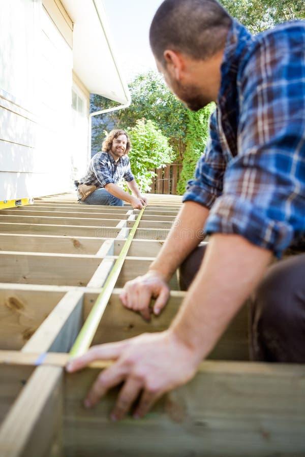 Fita de Measuring Wood With do carpinteiro ao olhar fotos de stock