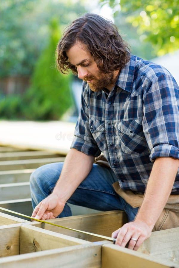 Fita de Measuring Wood With do carpinteiro na construção fotografia de stock