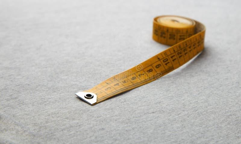 Fita de medição amarela na tela cinzenta imagens de stock