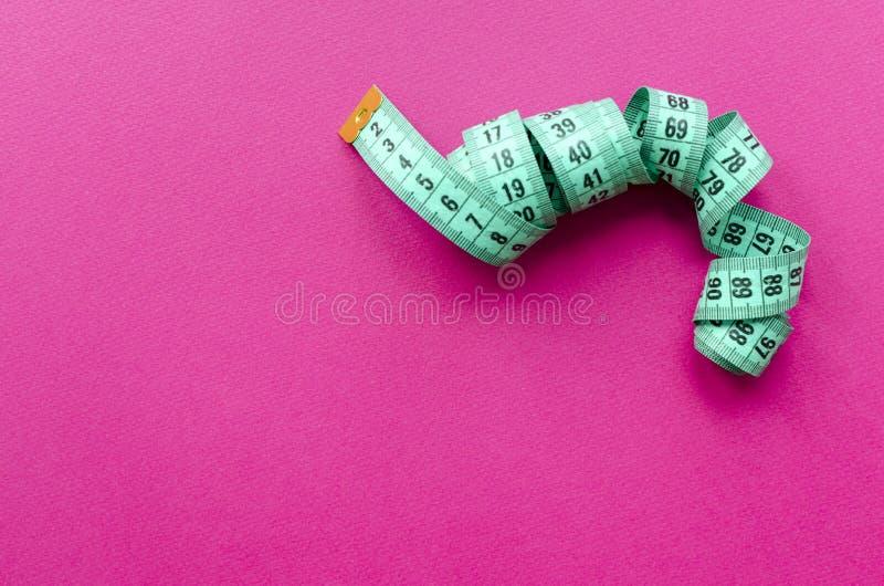 Fita de medição em um fundo cor-de-rosa fotografia de stock