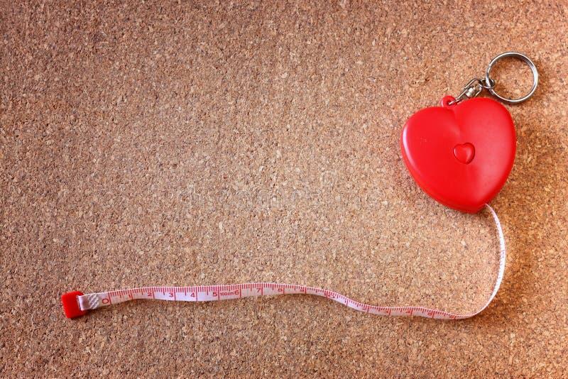 A fita de medição no coração rola sobre o corkboard. bom para o conceito da saúde ou do fittness. sala para o texto. imagens de stock royalty free