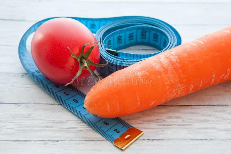 Fita de medição, tomate e cenoura suculenta, o conceito de comer saudável e peso perdedor imagens de stock