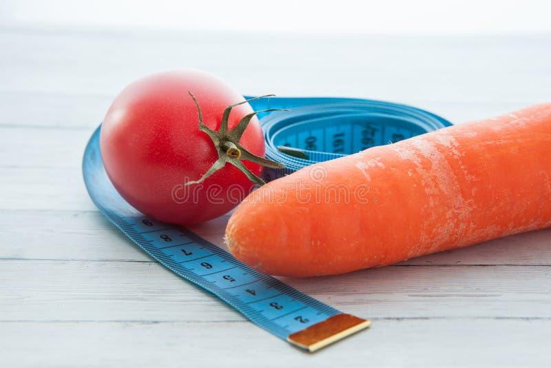 Fita de medição, tomate e cenoura suculenta, o conceito de comer saudável e peso perdedor foto de stock royalty free