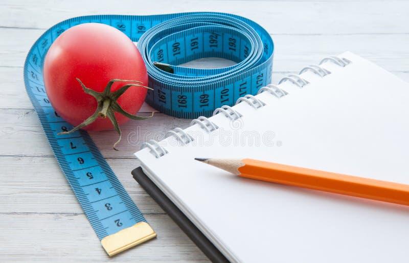 Fita e caderno de medição com tomates suculentos, o conceito de comer saudável e peso perdedor fotografia de stock
