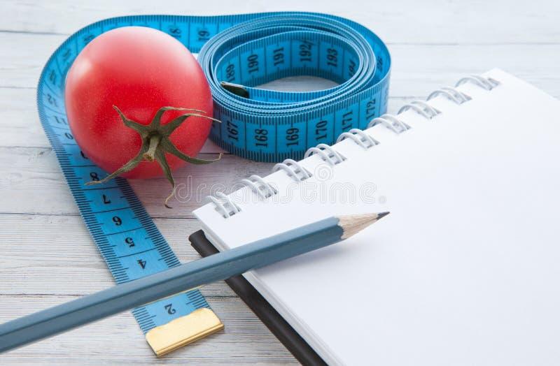 Fita e caderno de medição com tomates suculentos, o conceito de comer saudável e peso perdedor fotografia de stock royalty free