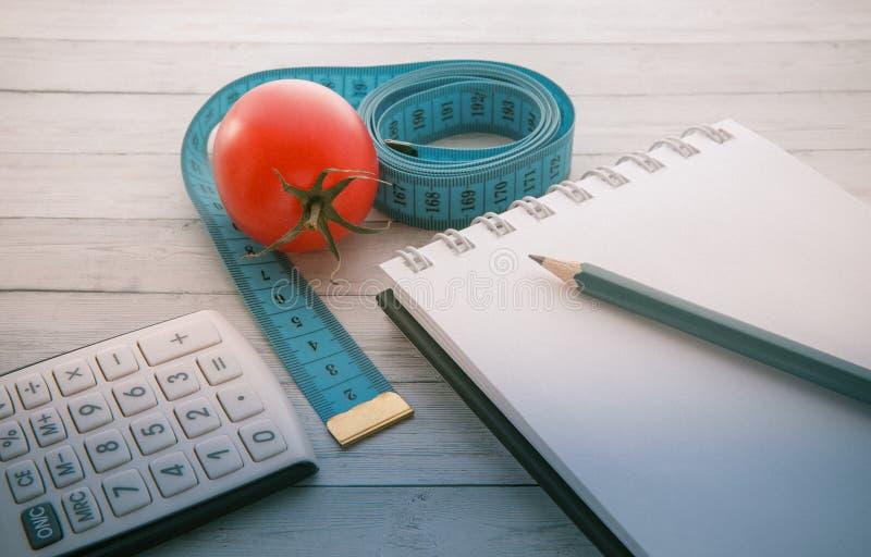 Fita e calculadora de medição com tomate suculento, conceito de comer saudável e emagrecimento imagem de stock