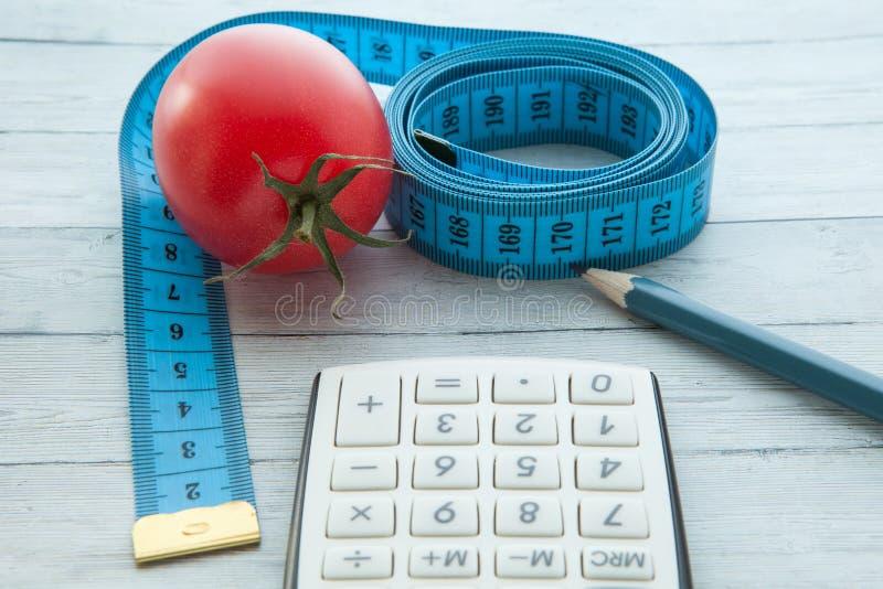 Fita e calculadora de medição com tomate suculento, conceito de comer saudável e emagrecimento, close-up imagem de stock royalty free