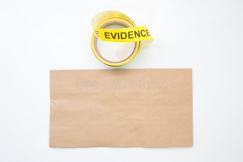 Fita e saco de papel do marcador da evidência na cena do crime isolada no wh foto de stock