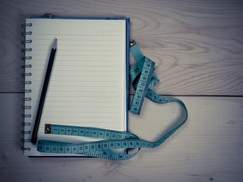 Fita métrica com o caderno para escrever notas imagens de stock