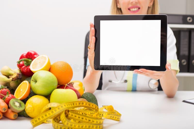 Fita métrica e vegetais na tabela e no doutor que guardam a tabuleta com tela vazia imagem de stock