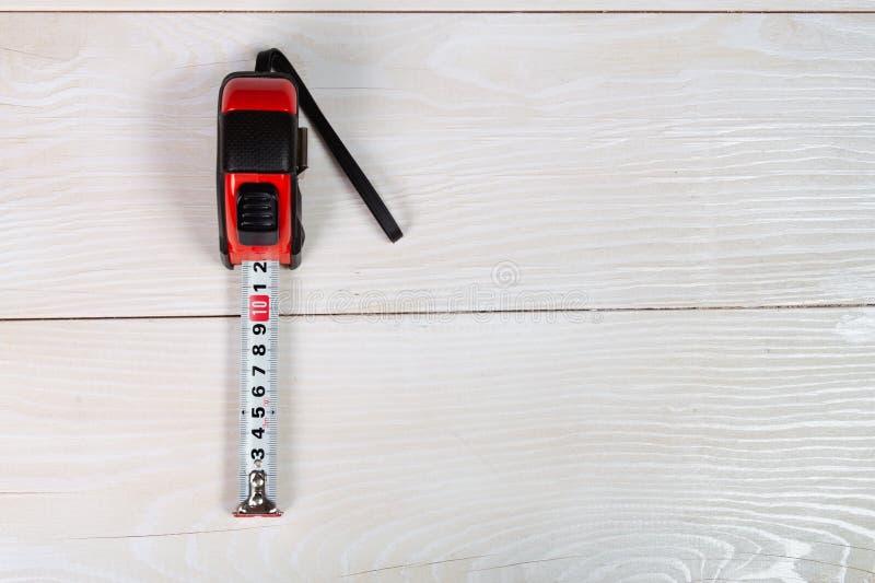 Fita métrica no fundo de madeira branco imagens de stock