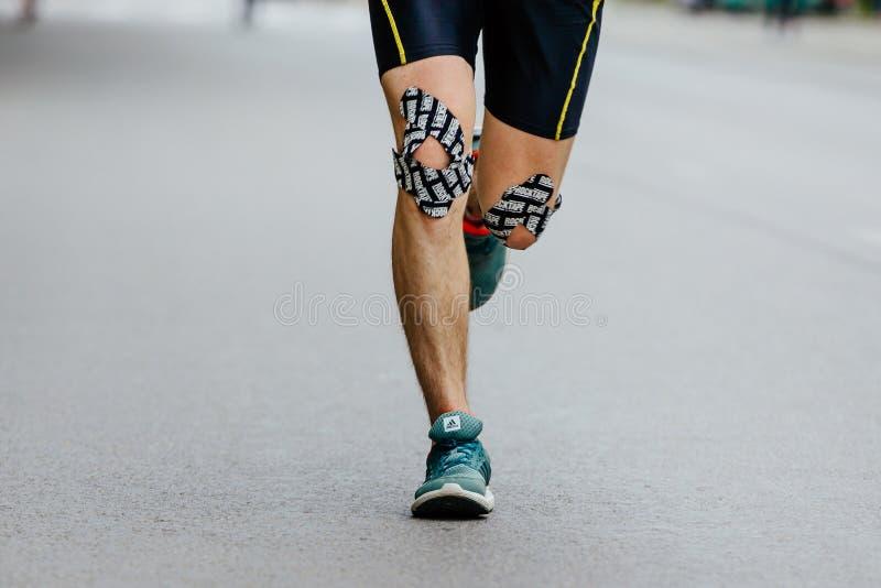 Fita masculina do kinesio do corredor dos joelhos do close up imagem de stock