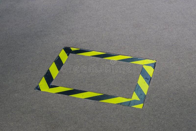 Fita preta e amarela colocada no tapete para evitar algum acidente foto de stock