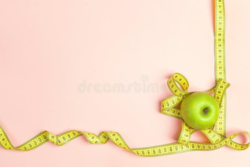 Fita verde do centímetro da maçã e do amarelo no fundo cor-de-rosa com s fotos de stock