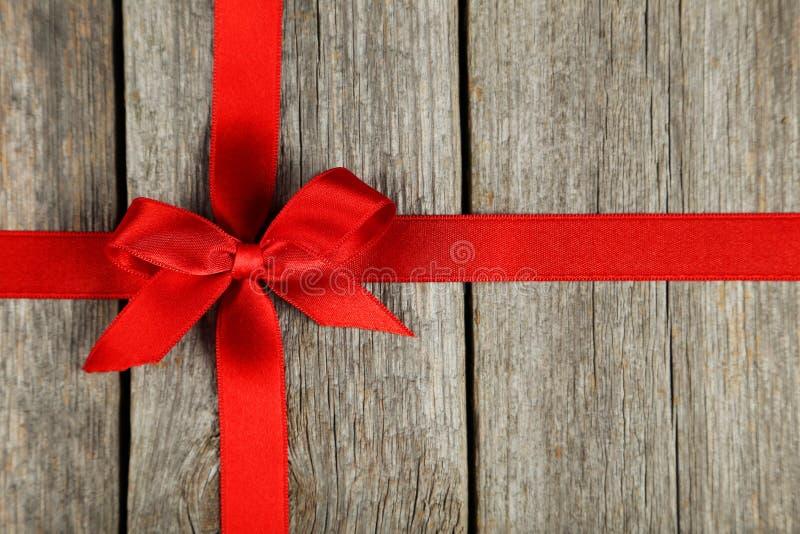 Fita vermelha com curva no fundo de madeira cinzento foto de stock