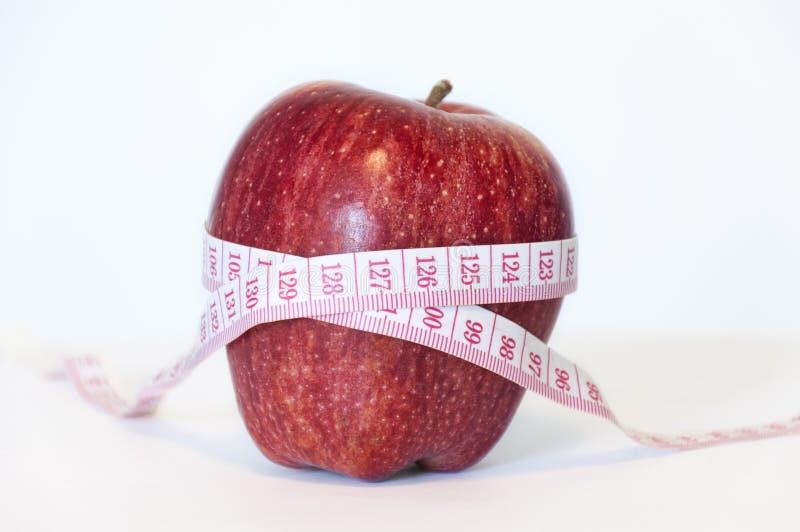 Fita vermelha da maçã e da medida fotografia de stock royalty free