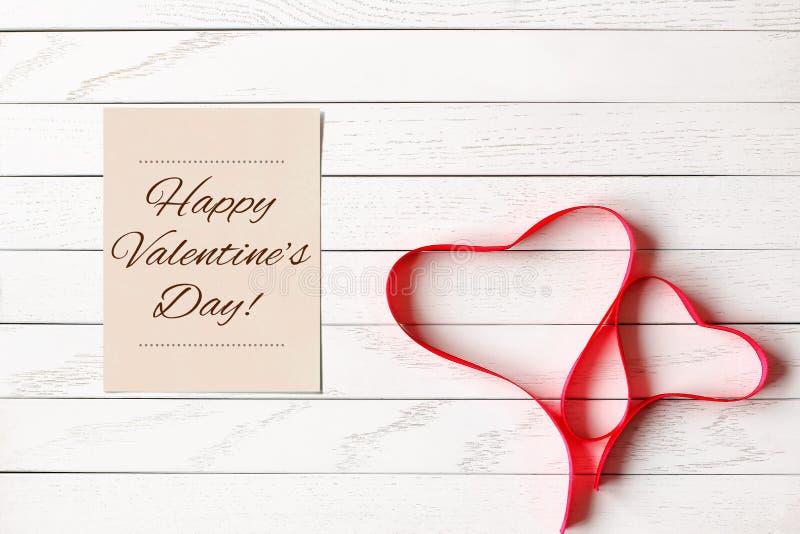 Fita vermelha do cetim em uma forma de dois corações no fundo de madeira imagens de stock royalty free