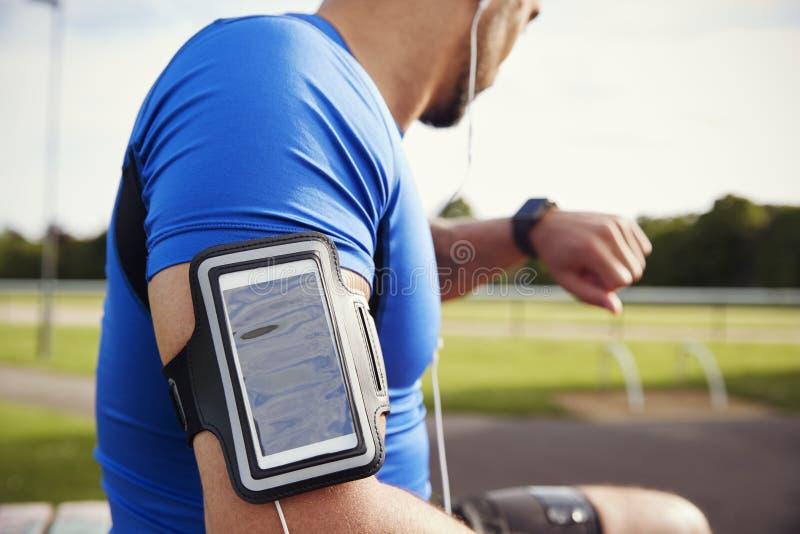 Fita vestindo do smartphone do atleta masculino que verifica o smartwatch fotos de stock