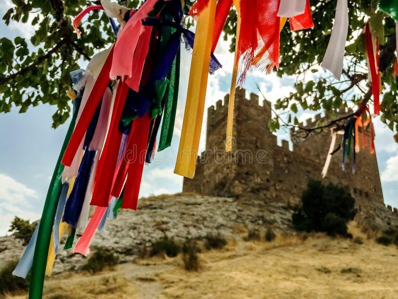 Fitas coloridas nos ramos da árvore como símbolo de fazer desejos, ao fundo está uma antiga fortaleza antiga e sua fotos de stock