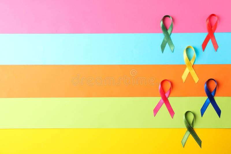 Fitas coloridos da conscientização no fundo multicolorido fotografia de stock