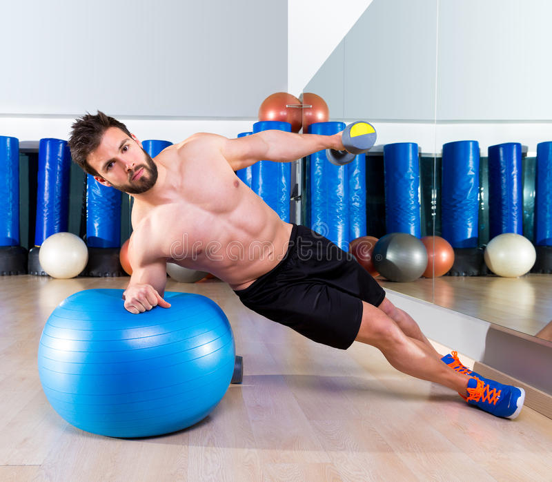 Fitball abdominal side push ups Swiss ball man. Pushup at fitness gym royalty free stock photos