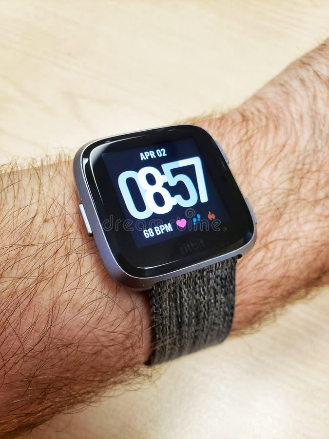 Fitbit Versa smartwatch på en mans arm arkivbild