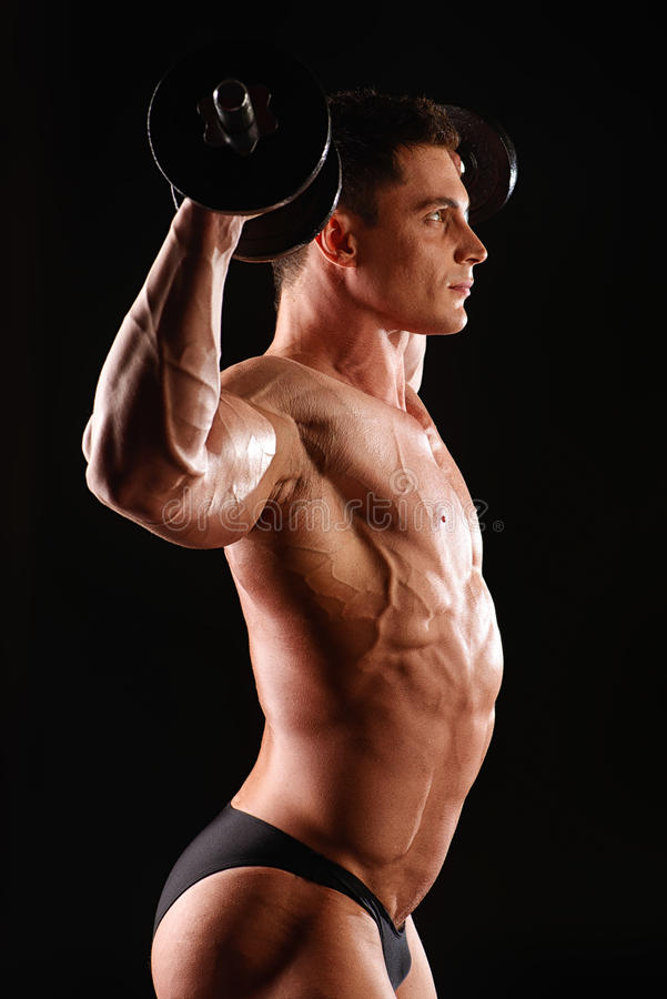 Fitman. Portrait of a handsome muscular bodybuilder posing with dumbbells over black background royalty free stock photo