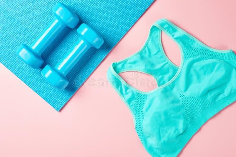 Fitnes简单派概念 哑铃和体育胸罩在蓝色和桃红色backgroundm顶视图 免版税库存图片