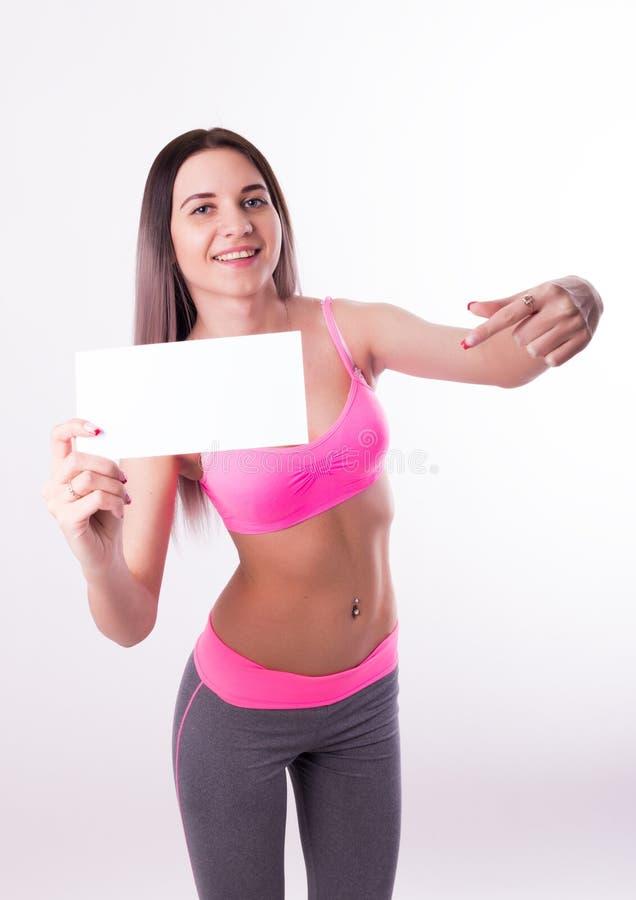 Fitnes atractivos morenos en un chándal que lleva a cabo al tablero blanco vacío imagen de archivo libre de regalías