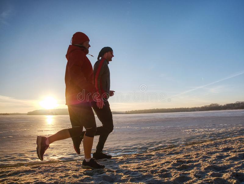 Fitnes couple man and woman. Winter landscape with sun royalty free stock photos