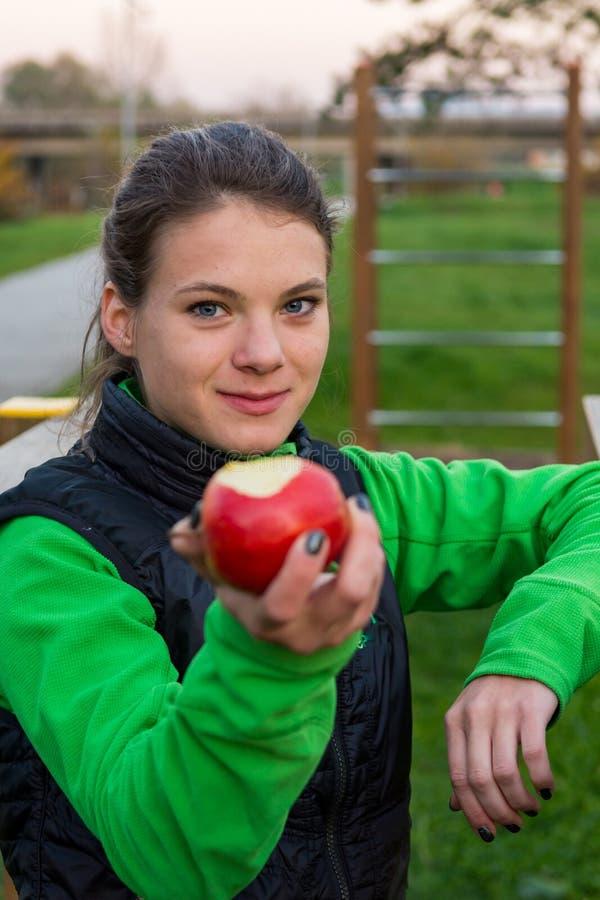 Fitnes instruktör som erbjuder ett äpple på den utomhus- idrottshallen royaltyfri fotografi