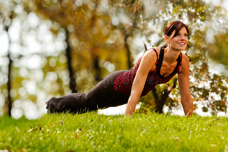Fitness. A caucasian female doing push ups in the park stock photography