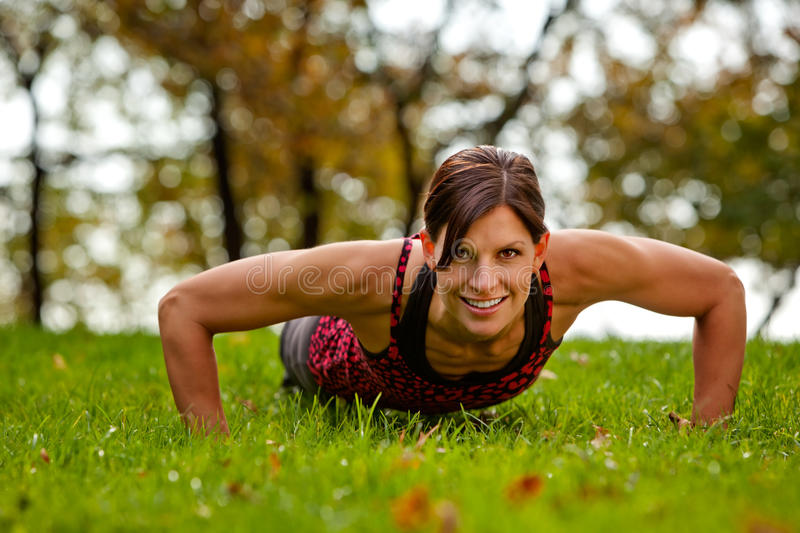 Fitness. A caucasian female doing push ups in the park royalty free stock photo