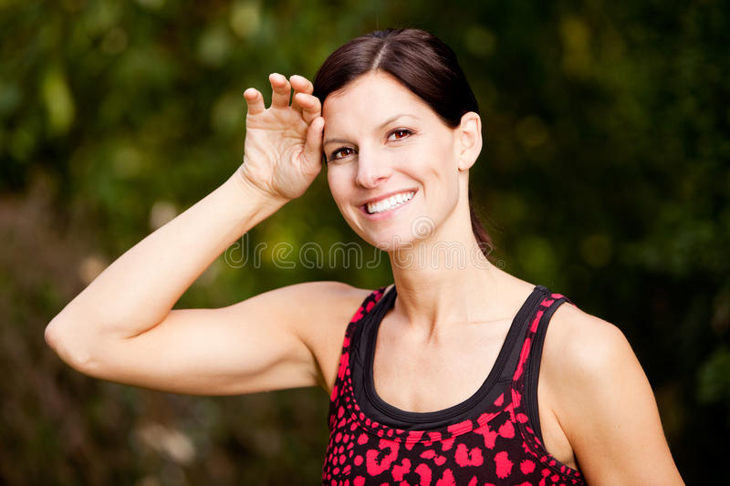 Fitness. A woman exercising in a park, taking a break royalty free stock images