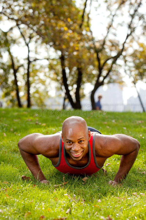 Fitness. An african american doing push ups in the park royalty free stock photography