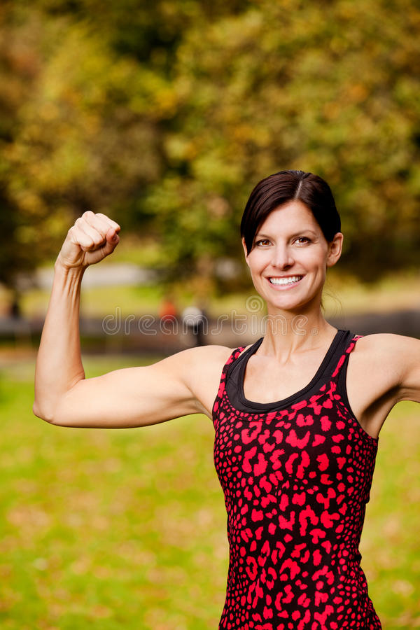 Fitness. A female fitness model flexing her bicep royalty free stock photos