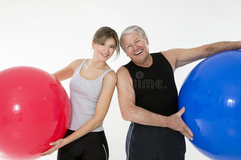 Fitness. Senior adult and daughter exercising with fitness ball in gym